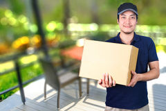 Asian smile Delivery man with cardboard box in hand standing on. Blurred outdoor restaurant background with dining table Royalty Free Stock Photography