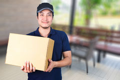 Asian smile Delivery man with cardboard box in hand standing on. Blurred outdoor restaurant background with dining table Royalty Free Stock Photo