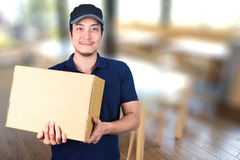 Asian smile Delivery man with cardboard box in hand standing res. Taurant blurred background with dining table Stock Image