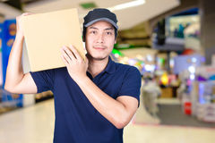 Asian smile Delivery man with cardboard box in hand standing in. Shopping mall or department store with blur bokeh background Stock Image