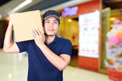 Asian smile Delivery man with cardboard box in hand standing in. Shopping mall or department store with blur bokeh background Stock Photography