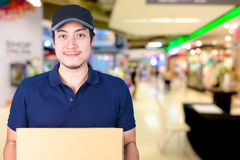 Asian smile Delivery man with cardboard box in hand standing in. Shopping mall or department store with blur bokeh background Stock Photos