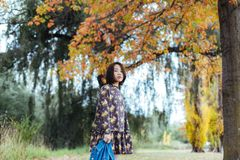 Asian female in autumn nature with jeans jacket. Asian smile woman standing under yellow trees in the park, looking at camera Royalty Free Stock Photography