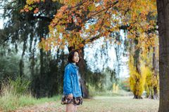 Asian female in autumn nature with jeans jacket. Asian smile woman standing under yellow trees in the park, looking at camera Stock Photography