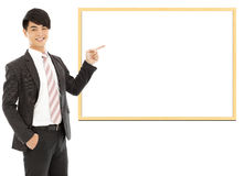 Asian smiling businessman pointing blank board Stock Photo