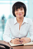 Asian smiling businesswoman sitting at table holding ballpoint p. Ent and looking at  camera Royalty Free Stock Photo
