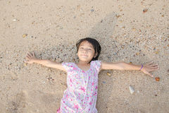 Asian smiling cute little girl lying on the beach sand. Thai chi Royalty Free Stock Photo
