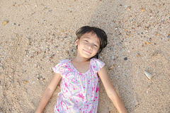 Asian smiling cute little girl lying on the beach sand. Thai chi Stock Image