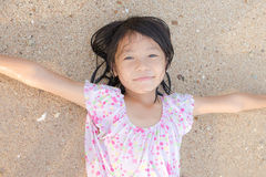 Asian smiling cute little girl lying on the beach sand. Thai chi Stock Photo