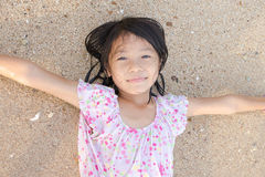 Asian smiling cute little girl lying on the beach sand. Thai chi Royalty Free Stock Photography