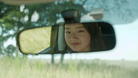 Woman looking at reflection in car rearview mirror. Asian smiling female driver looking at her reflection in the rearview mirror of car during summer vacations stock footage