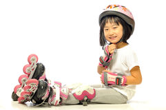 Asian smiling little girl is wearing roller blades Stock Images