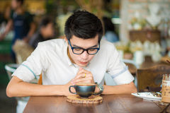 Asian smiling man with cup of latte art coffee indoor Stock Photos