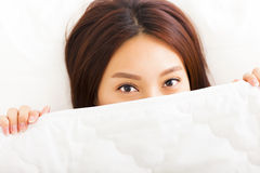 Asian smiling woman in bed Royalty Free Stock Image
