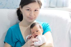 Asian smiling woman holding infant baby in her arms, happy motherhood. Asian smiling women holding infant baby in her arms, happy motherhood concept Stock Images