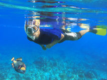 Asian snorkel and big fish under blue water during snorkeling lesson near coral reef. Snorkeling with triggerfish, indonesian snorkel in mask, diving to coral Stock Images