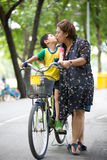 Asian Son on bicycle is kissing his mother in the park Stock Photos
