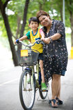 Asian Son on bicycle is smile with his mother in the park. Bangkok Thailand royalty free stock image