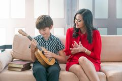 Asian son plays a Hawaiian string quartet with his mother in the stock images