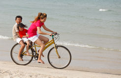 Asian sons and mother riding bicycle on beach Stock Images