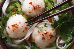 Asian soup with fish balls and chopsticks macro top view Royalty Free Stock Images