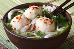 Asian soup with fish balls, fresh herbs and rice noodles close-up royalty free stock image