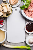 Asian soup ingredients with diced tofu and sliced meat around blank white cutting board Royalty Free Stock Image