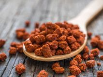 Asian spices. Dry adjika in spoon on wooden background. Closeup stock photography