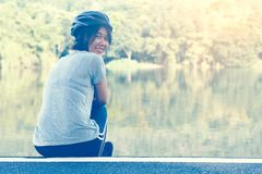 Asian Woman Ride Bicycle. Asian Sport Woman with Cycling Helmet Acting near the Lagoon Royalty Free Stock Photos
