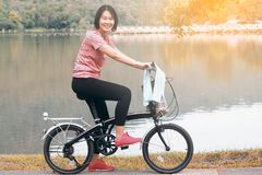 Asian Woman Ride Bicycle. Asian Sport Woman with Cycling Helmet Biking Bicycle near the Lagoon Stock Images