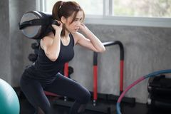asian sport woman in sportswear exercise squat with with training weight bag in fitness gym . young girl workout with lifting wei royalty free stock images