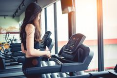 Asian sport woman walking or running on treadmill equipment in f. Itness workout gym. Sport and Beauty concept. Workout and Strength Training theme. Cardio and Royalty Free Stock Photo