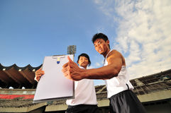 Asian Sports Duo and Blank Clipboard royalty free stock photos