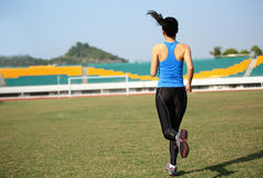 Asian sports woman running in stadium Royalty Free Stock Image