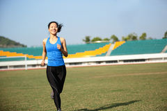Asian sports woman running in stadium Royalty Free Stock Photos
