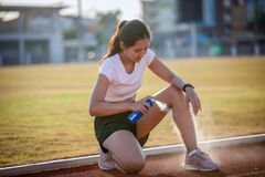 Asian Sports women using freezing spray for treating injured sportwomen`s knee and leg  after run