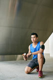 Asian sportsman sitting on haunches Royalty Free Stock Images
