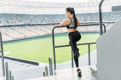 Asian sportswoman in sportswear stretching at handrail on stadium. Young asian sportswoman in sportswear stretching at handrail on stadium Stock Image