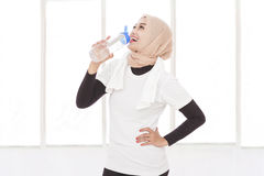 Asian sporty woman drinking mineral water after workout Royalty Free Stock Photography