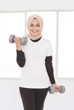 Asian sporty woman lifting weight using dumbbells. Portrait of asian sporty woman lifting weight using dumbbells while smiling Stock Photos