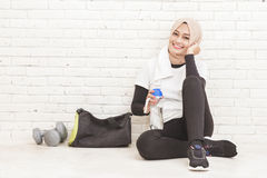 Asian sporty woman sitting on the floor resting after workout Stock Photo