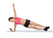 Asian sporty woman with smartphone doing exercise Stock Image