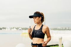 Asian sporty woman wear sport bra running outdoors along river s. Idewalk morning and listening to music with earphones in summer  warm ligh Stock Images