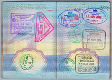 Asian stamps in a passport. Passport pages of a traveller who frequently travels to Asia. The stamps are from Cambodia, Malaysia and Singapore Royalty Free Stock Photography