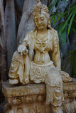 Asian Statue Seated Female. Found this beauty in the corner of a tropical garden on Maui. The seated female statue has several large cracks that add to the royalty free stock photography