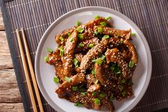 Asian stir-fried beef in teriyaki sauce with sesame and green on. Ions closeup on a plate on the table. horizontal top view from above stock image