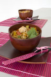 Asian Stir Fry. Two sets of stir fry in bamboo bowls with chopsticks on pink place mats Royalty Free Stock Photography