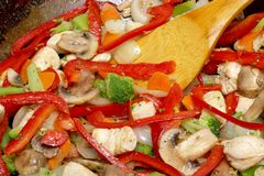 Asian Stir Fry Cooking. Asian-style stir-fry featuring red peppers and chicken, being cooked in a wok stock images