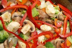 Asian Stir Fry Cooking. Closeup detail of a chicken and vegetable stir-fry cooking in a wok royalty free stock photo
