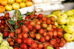 Asian street farmer market selling riped rambutan in Vietnam. Asian street farmer market selling fresh fruit in Hoi An, Vietnam. Rambutan and mango. Yellow and Royalty Free Stock Images